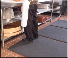 Man standing on anti fatigue mat in kitchen